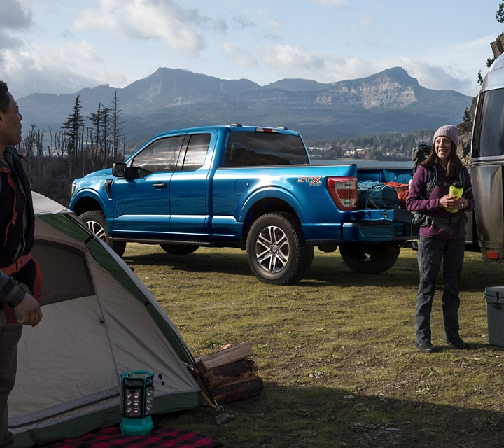 A group of friends grilling at a campsite near a 2021 Ford f one fifty