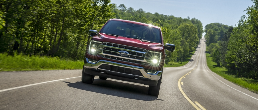 Front view of a 2021 Ford F 1 50 driving down a long country road
