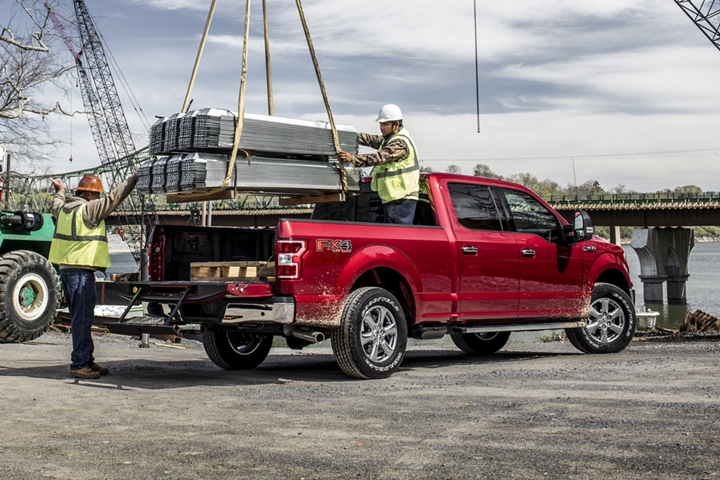 Workers loading heavy cargo into bed of 2020 Ford F 1 50