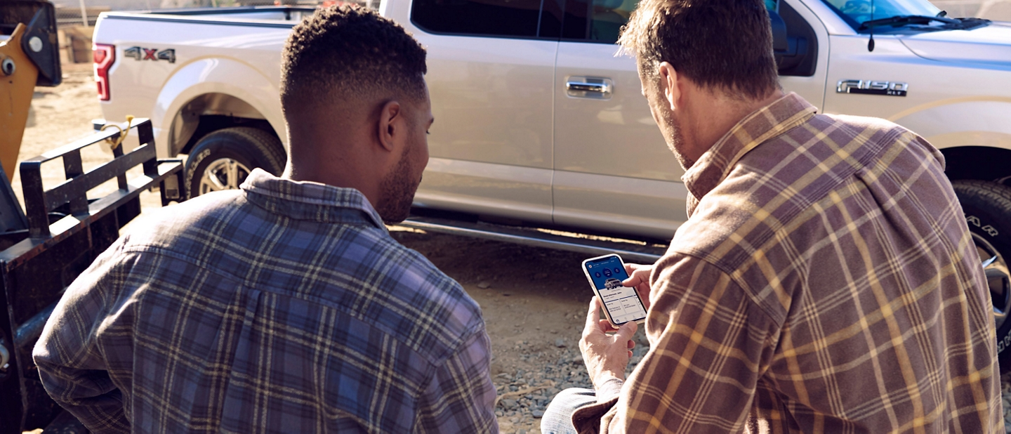 Two men sitting on a job site looking at the Ford Pass Connect app on a smart phone