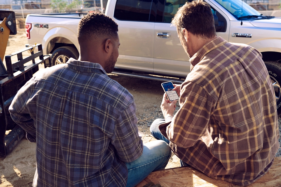 Two men sitting on a work site using Ford Pass Connect app on a smart phone