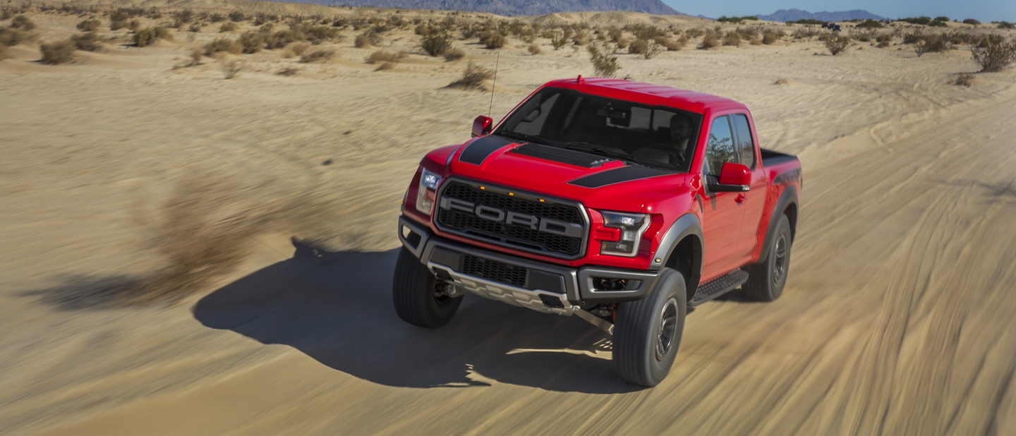 2020 Ford F 1 50 Raptor in Race Red tearing through the desert terrain