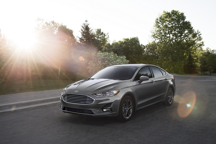 2020 Ford Fusion being driven on a suburban road while the sunset behind