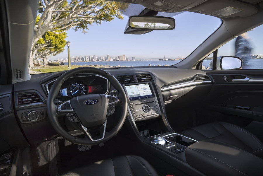 Behind the wheel of the 2020 Ford Fusion looking out at a body of water with a cityscape in the background