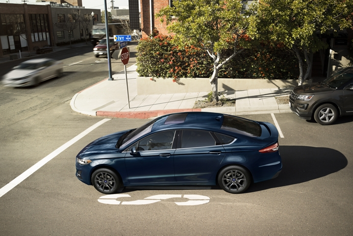 2020 Ford Fusion shown with the S E appearance package stopped at an urban intersection
