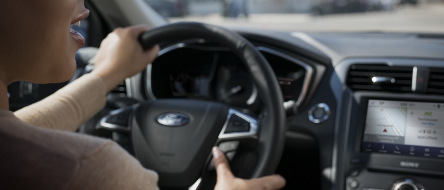A woman driving a 2020 Ford Fusion is shown using the steering wheel buttons