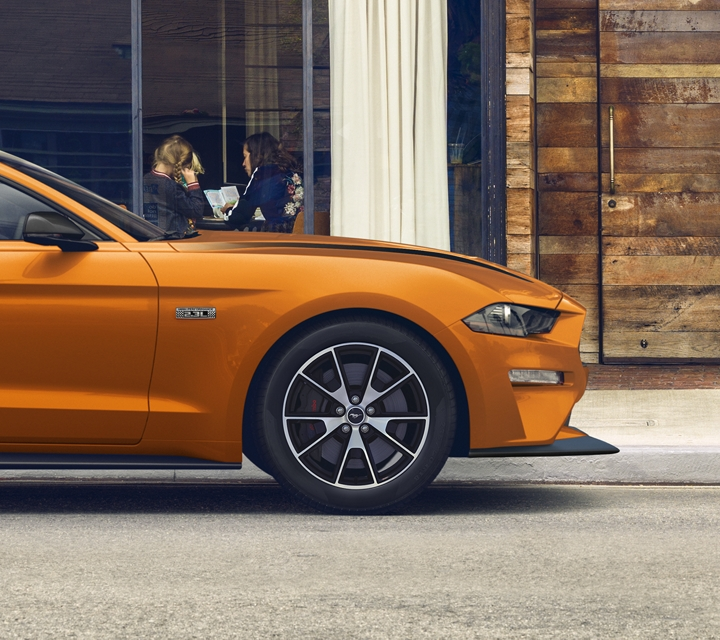 A side profile view of the 2020 Ford Mustang G T in twister orange parked in front of a store front