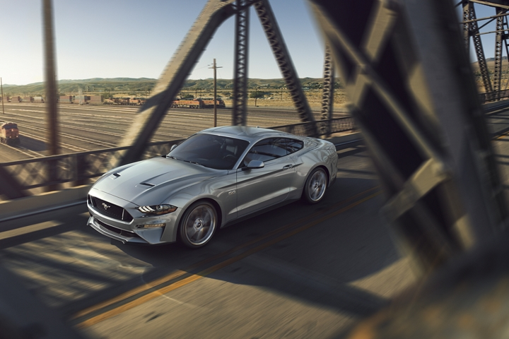2020 Ford Mustang G T in Iconic Silver driving across a metal bridge over a train yard