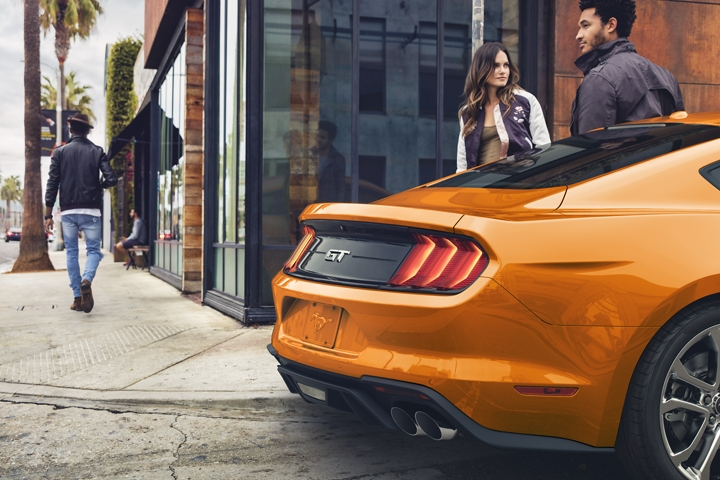 Rear shot of a 2020 Ford Mustang in Twister Orange Metallic tinted clearcoat parked on a city street