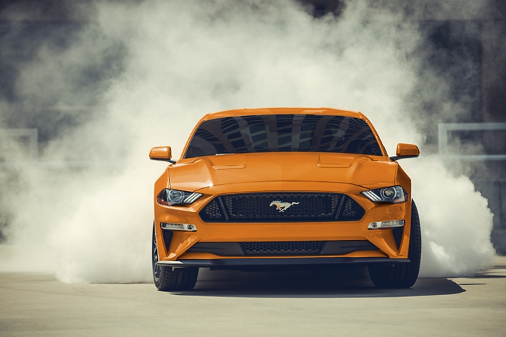 2020 Ford Mustang G T in Twister Orange Metallic tinted clearcoat doing a burnout with smoke surrounding the rear tires