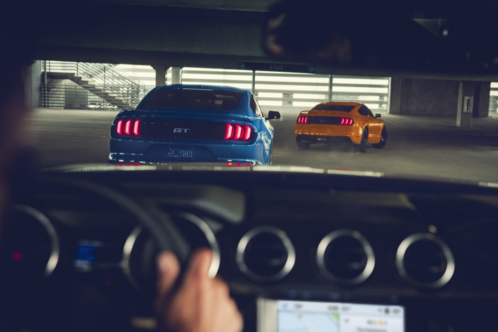 Interior view out the front window of a 2020 Ford Mustang looking at two other mustangs in a parking garage