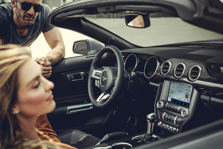 A man and woman in a 2020 Ford Mustang featuring the new Carbon Sport Interior Package