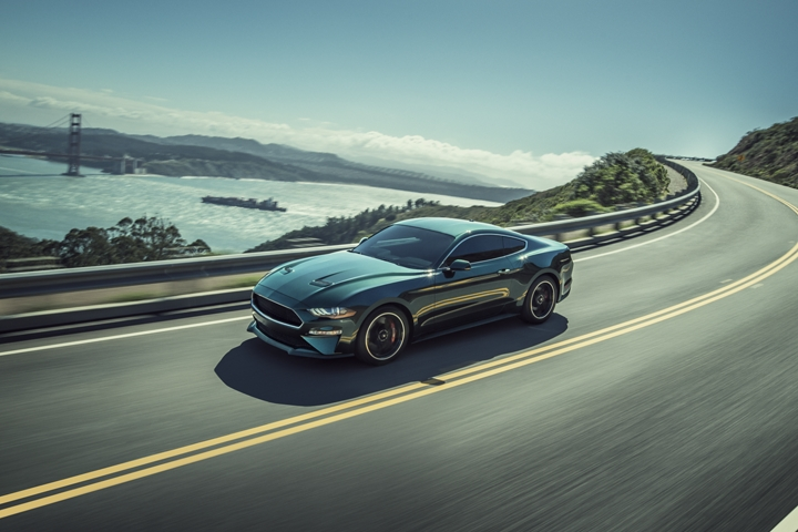 2020 Ford Mustang BULLITT going around a curve with a bridge in the background