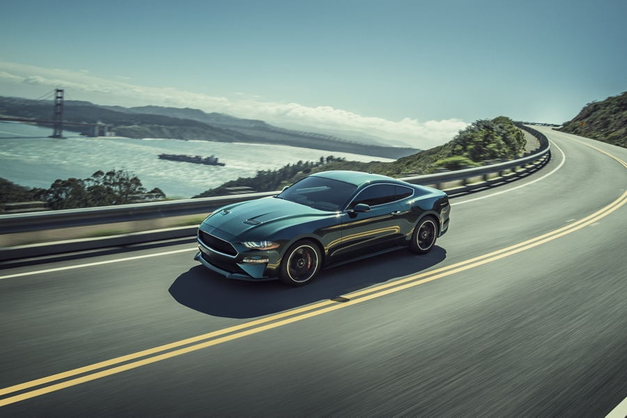 A 2020 Ford Mustang BULLITT being driven around a curve with a bridge in the background