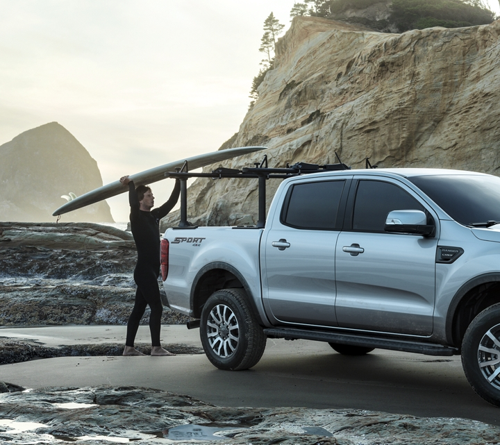 A surfer is loading his surfboard into the bed of the Ranger shown in Ingot silver