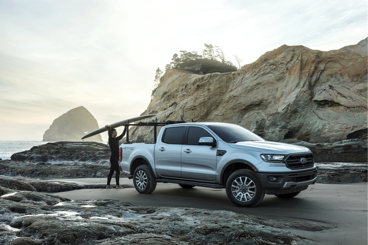 2019 Ford Ranger parked on an oceanfront beach with a man pulling a surf board off a rack from the truck bed