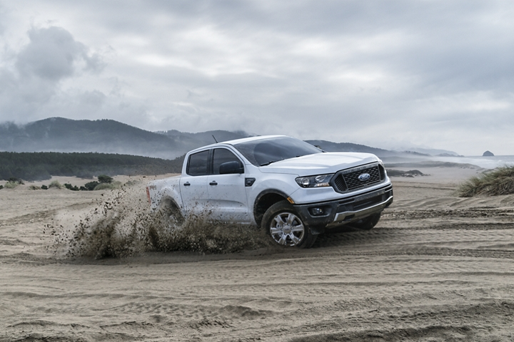 2019 Ford Ranger four wheeling on a sandy beach close to the ocean