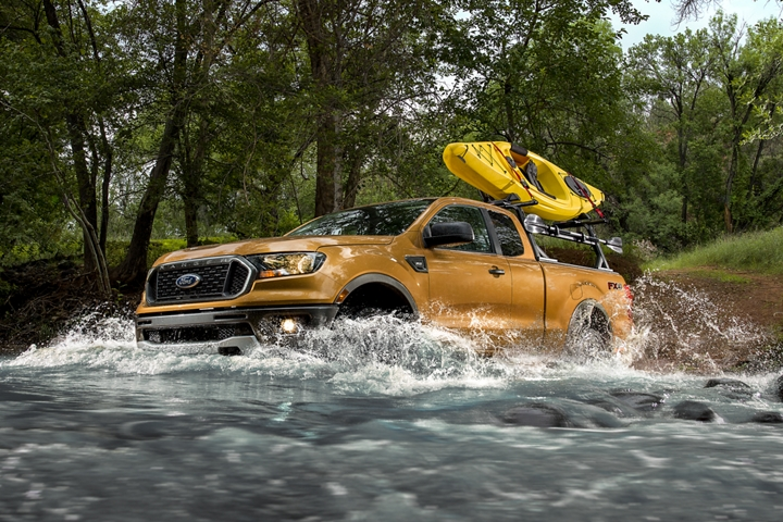 A Ranger is driving through a shallow river with a kayak on a rack in the bed