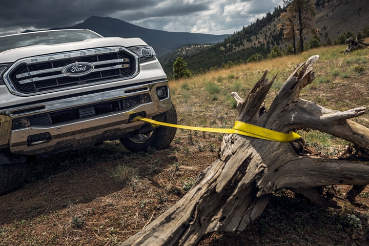 2019 Ford Ranger using its exposed front tow hooks with a rope to move a large tree stump