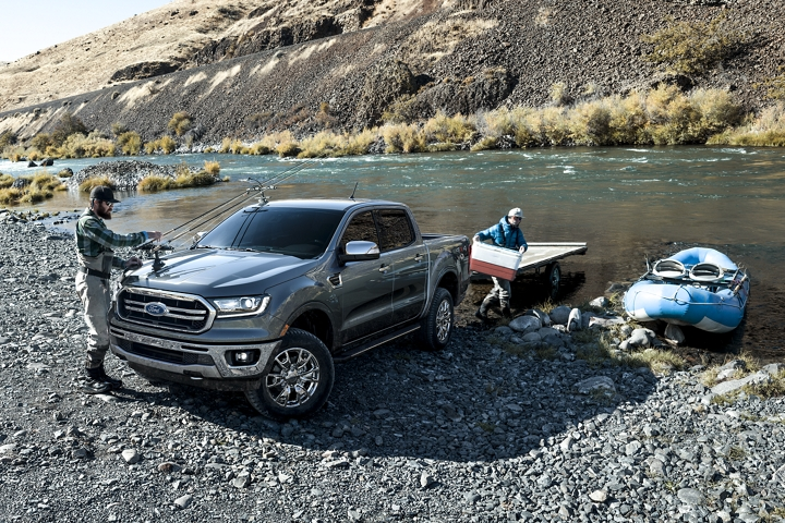 Men at river bank unloading rubber raft from trailer on 2020 Ford Ranger