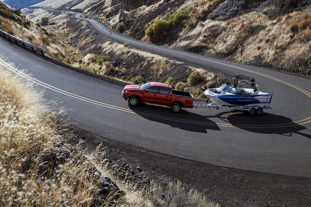 2020 Ford Ranger on a twisting mountain road with a boat in tow