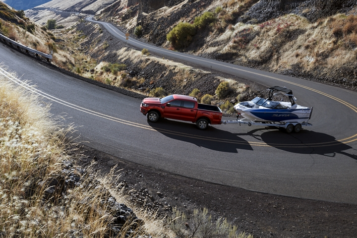 2020 Ford Ranger on sharply curved paved road towing a boat