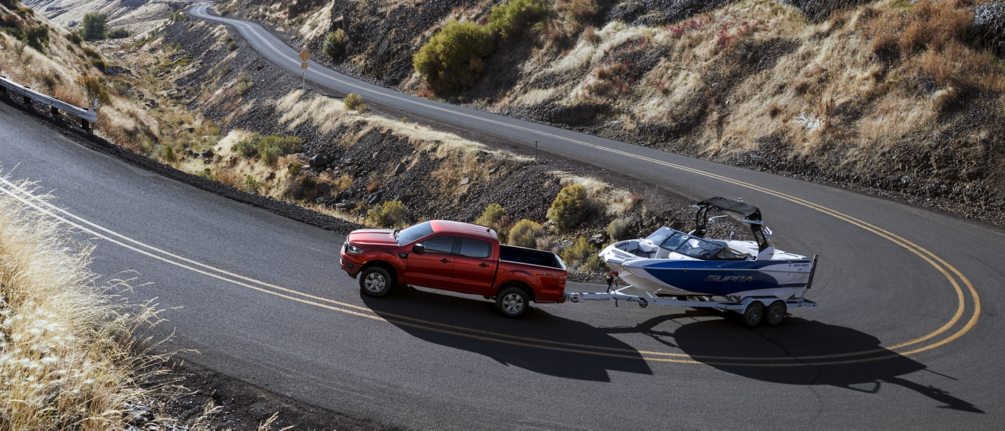 2020 Ford Ranger in Rapid Red Metallic Tinted Clearcoat on a curved road towing a boat