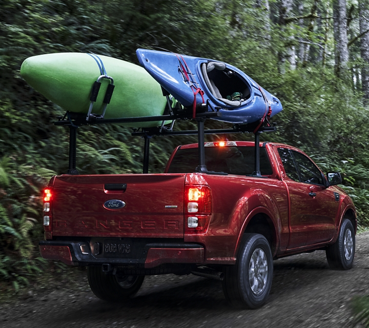 2020 Ford Ranger shown in Rapid Red Metallic Tinted Clearcoat loaded with kayaks on a forest road