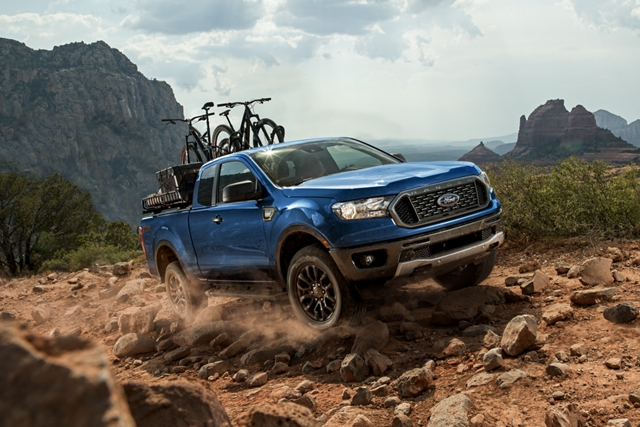 2020 Ford Ranger in Lightning Blue on rocky terrain with trail bikes on pickup bed rack