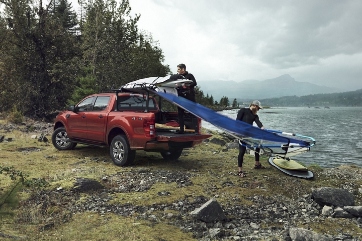 Two men unloading wind surfing equipment out of the bed of a 2020 Ford Ranger