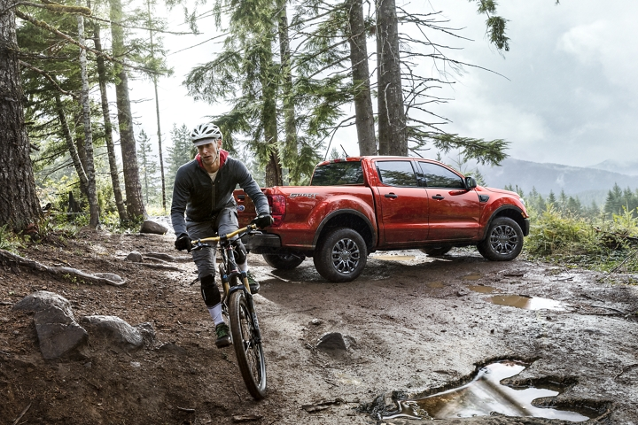 2020 Ford Ranger XLT in Race Red in the outdoors with mountain biker