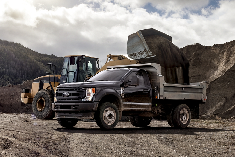 A backhoe fills the bed of an F 600 Super Duty on a construction site