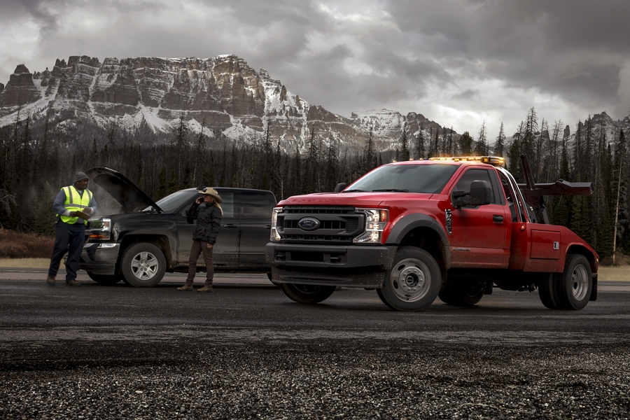 An F 450 Super Duty tow truck in Race Red helps someone broken down on the road
