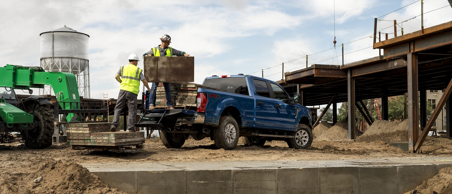 Workers loading cargo into pickup bed of 2020 Ford Super Duty