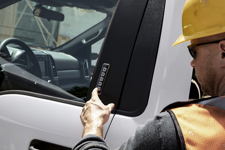 A man with a work hat and safety vest keying his code into keyless entry keypad