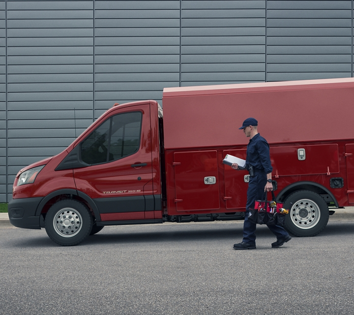 2020 Ford Transit Cutaway mechanics truck upfit in front of large building with worker walking towards van
