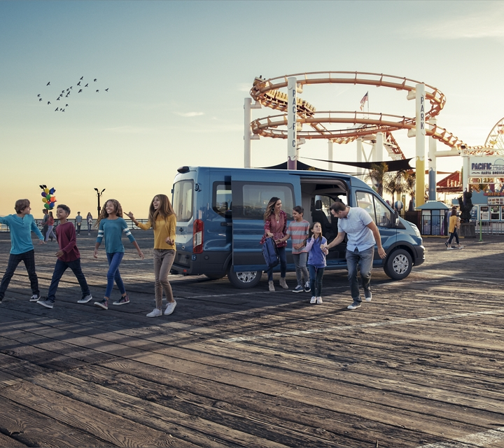 A large family arrives at an amusement park in a transit passenger van