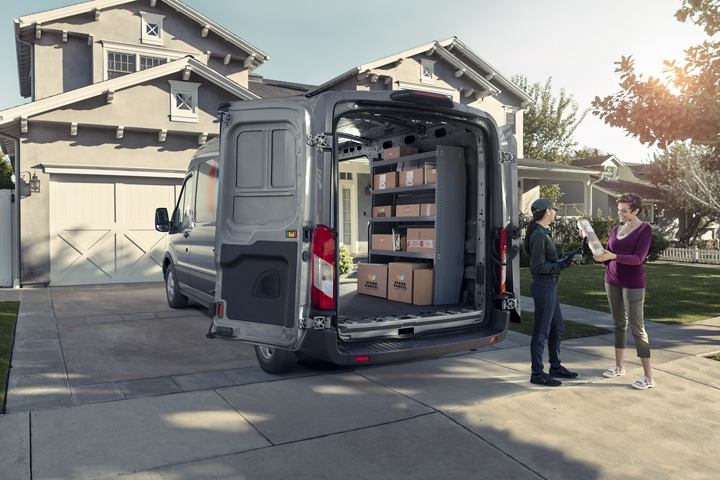 Rear view of a 2020 Transit Cargo Van parked in a driveway with the side and cargo doors open