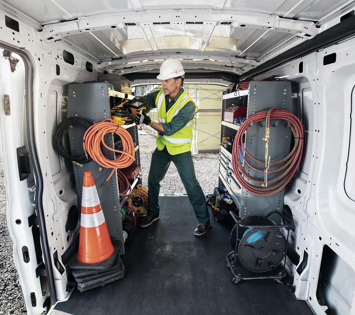 A workman obtains equipment from a transit cargo van