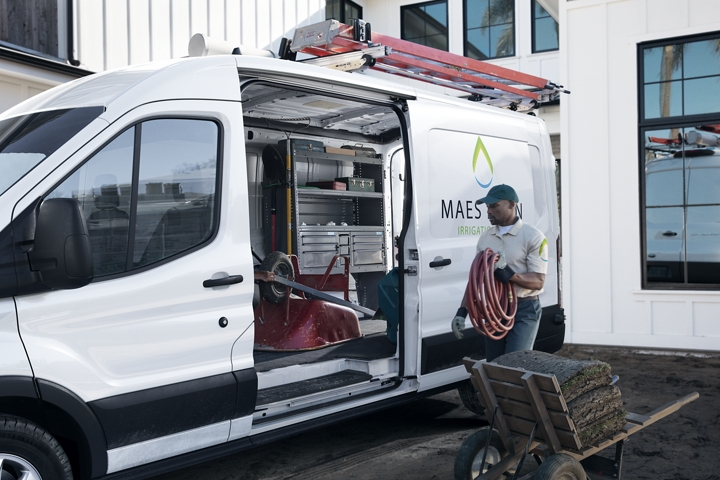 View of a parked 2020 Ford Transit Cargo Van with the doors open and a worker loading equipment