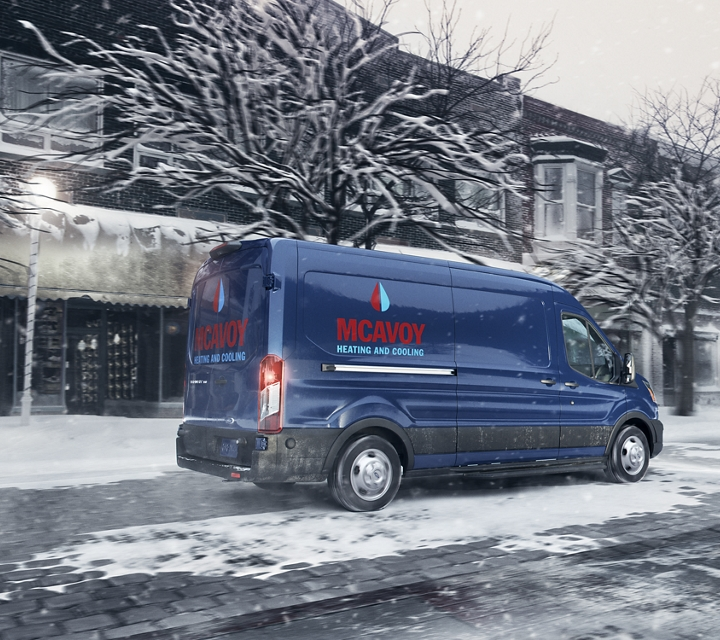 A heating and cooling transit cargo van at work on a snowy day