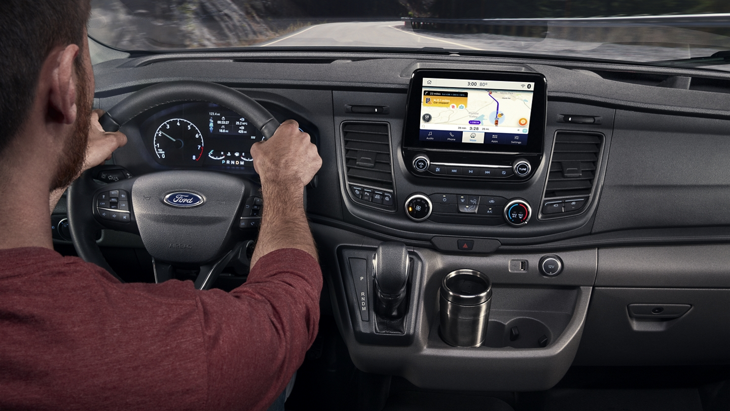 A man behind the wheel of a 2020 Ford Transit using the navigation system