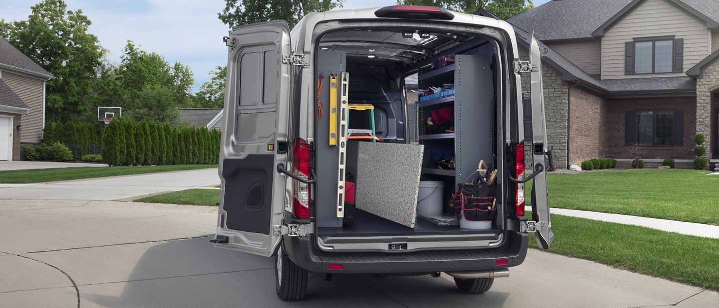 A 2020 Ford Transit with open cargo doors showing construction equipment