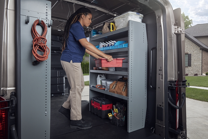A person in the back of a 2020 Ford Transit with open cargo doors
