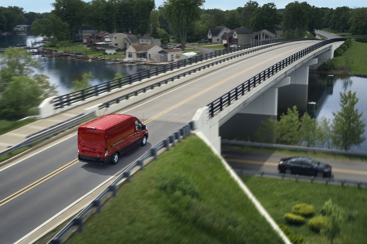 A 2020 Ford Transit in Race Red being driven across a bridge