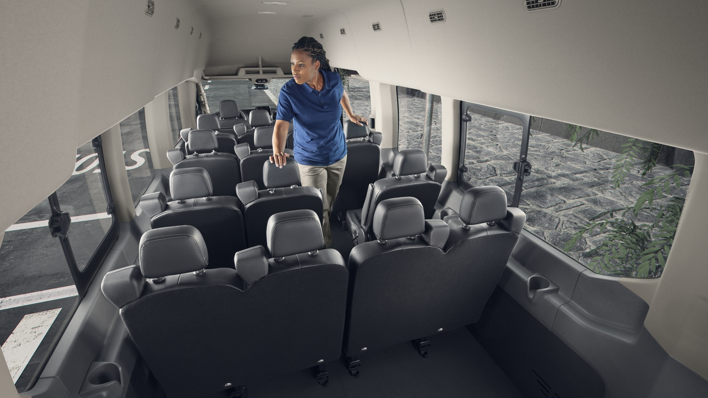 A woman stands in the 2020 Ford Transit interior with seating for 15