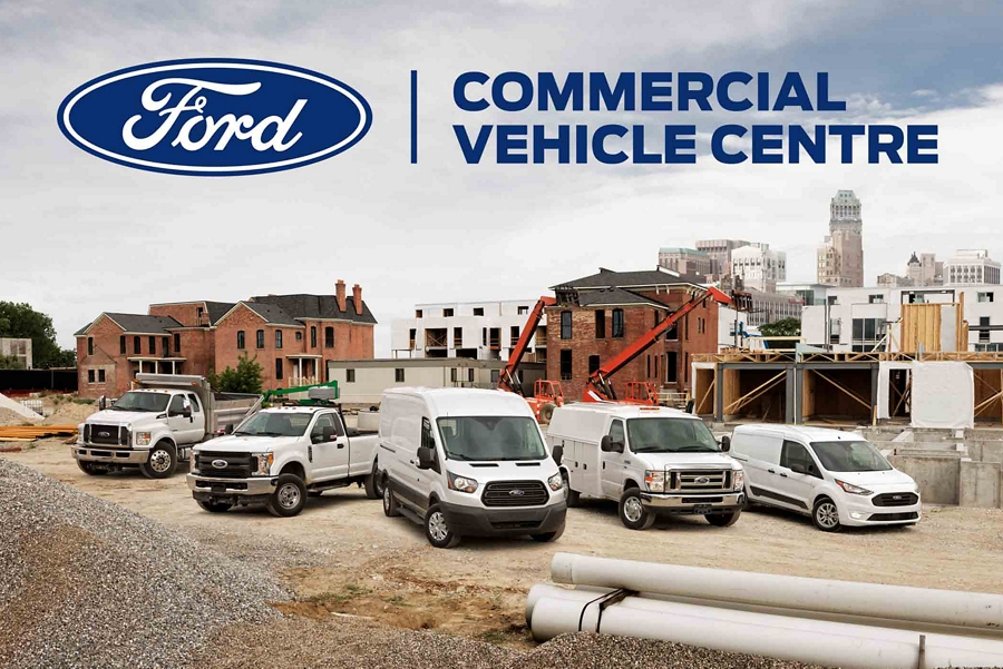 A row of commercial vehicles with a Ford Commercial Vehicle Centre billboard in the background