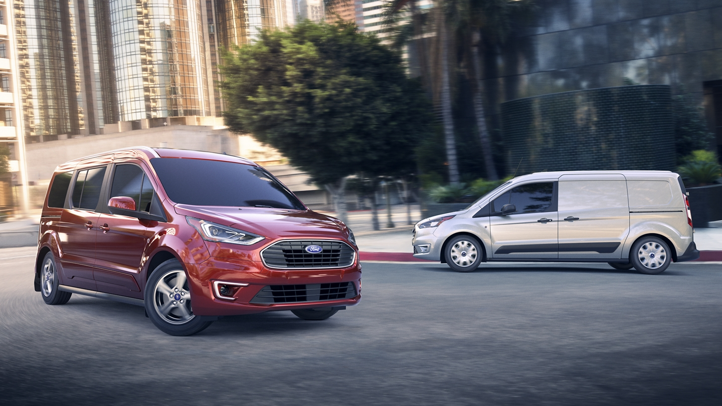 A 2020 Ford Transit Connect Passenger Wagon in Kapoor Red and a 2020 Ford Transit Connect Cargo Van in Diffused Silver on the street