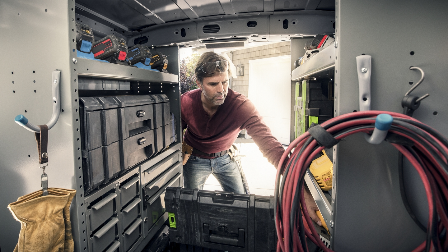 View of cargo space in capable 2020 Ford Transit Connect Cargo Van with man on the job