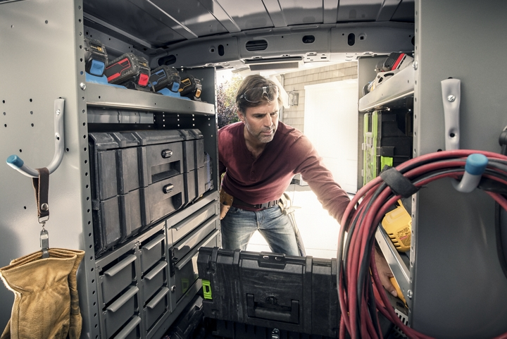 Man at work in the back of a 2020 Ford Transit Connect with aftermarket upfitted shelving
